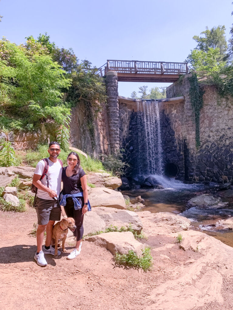 Guy and girl standing with their dog in front of a waterfall on one of the hiking trails on the Biltmore Estate in Asheville